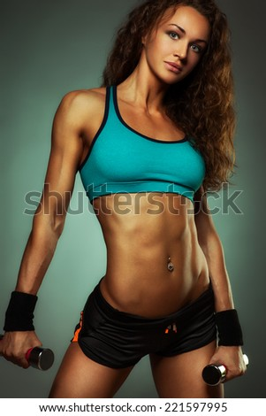 Young sports woman with dumbbells. - stock photo
