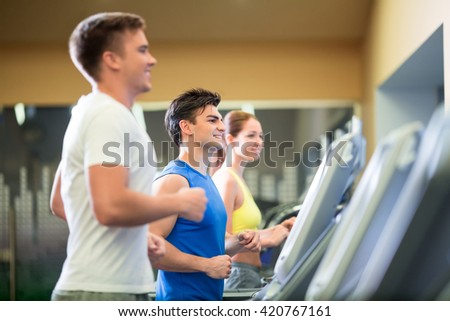 Young sportsman at treadmill indoors