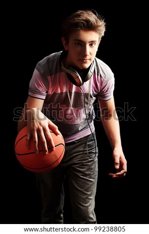 Young sportsman basketball player moving with ball. Over black background. - stock photo
