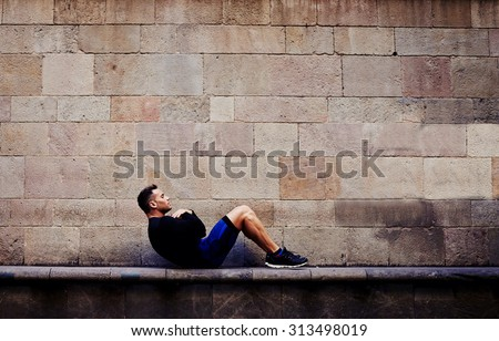 Young sportsman doing abdominal crunches against brick wall with copy space area for your text message or advertising content, sporty guy engaged an intensive fitness training in urban setting - stock photo