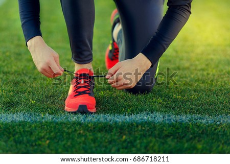Young sportsman dresses his shoes in training on a green football field