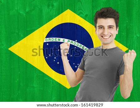 young sportsman fan cheering against the Brazilian flag - stock photo