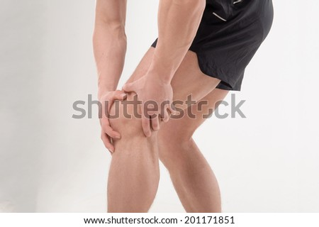 Young  sportsman, fitness muscle model guy feeling pain in his knee isolated on white background. Concept of sport, trauma - stock photo