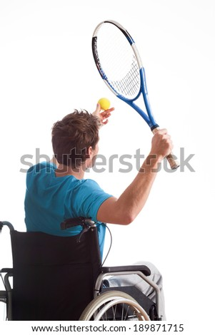 Young sportsman in wheelchair with tennis racket in hand - stock photo