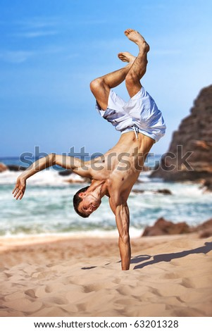 Young sportsman on beach standing on hand upside down. - stock photo