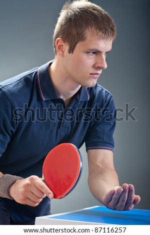Young sportsman playing table tennis - stock photo