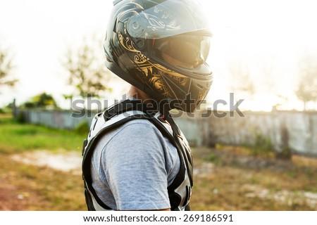 Young  sportsman posing on helmet opposite the sunset.Motocross man,sportsman on motorcycle wear helmet,motocross clothes ,cool motorcycles man in sunglasses and helmet - stock photo