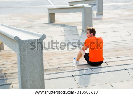 Young sportsman resting after an active fitness training sitting on the steps in urban setting, male runner enjoying city view while taking break after workout outdoors, athletic men having rest - stock photo