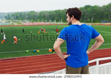 Young sportsman runner in blue shirt looking at stadium football field after training with hands on belt