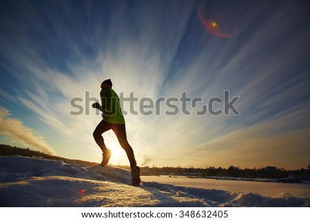 Young sportsman running in snow in rural environment
