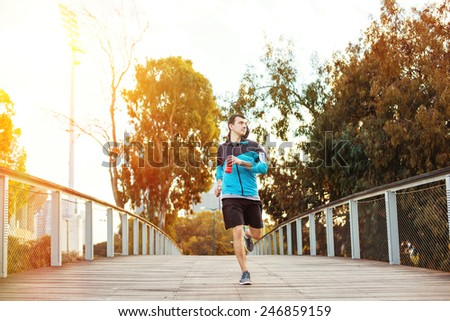 young sportsman running in the park over wooden bridge and bright sunset behind him - stock photo