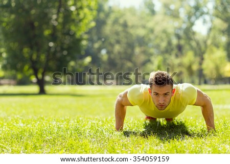 Young sportsman working-out in a park, doing a series of push ups - stock photo
