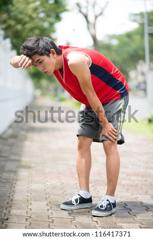 Young sportsmen taking breath - stock photo