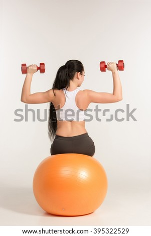 Young sportswoman doing fitness exercise with dumbbells on pilates ball