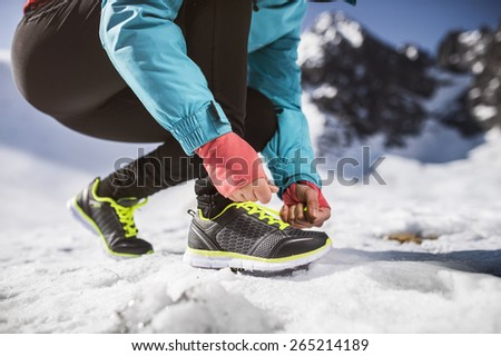 Young sportswoman jogging outside in sunny winter mountains - stock photo