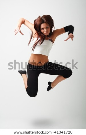 Young sportswoman jumping against gray background