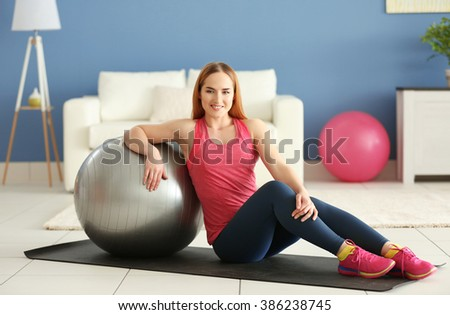 Young sportswoman sitting with ball on a mat at home