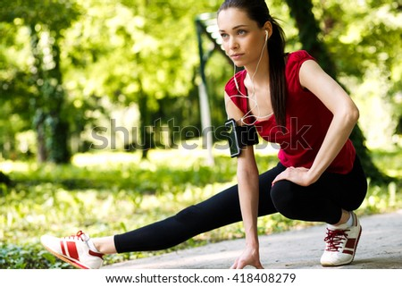 Young sportswoman stretching and preparing to run in park. - stock photo