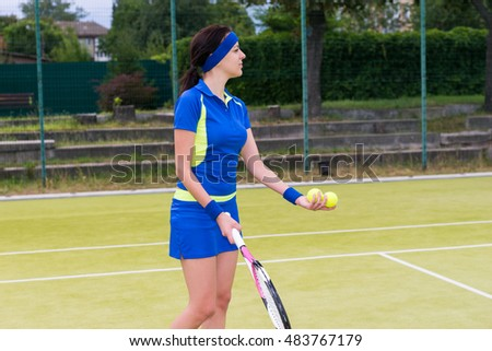 Young sportswoman wearing a sportswear holding tennis balls and a racket during a match on a court outdoor in summer or spring