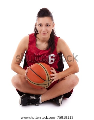 Young sportswoman with basketball sitting on white background. - stock photo