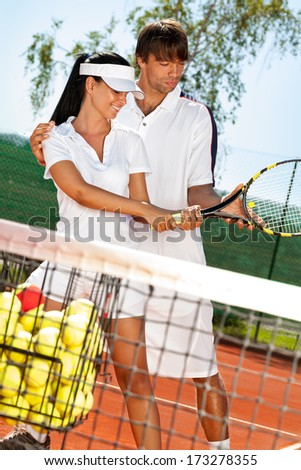 young sportswoman with coach practicing tennis - stock photo
