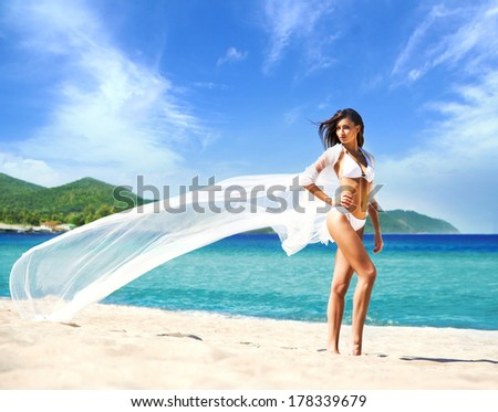 Young, sporty and happy woman posing with a blowing silk on a summer beach - stock photo