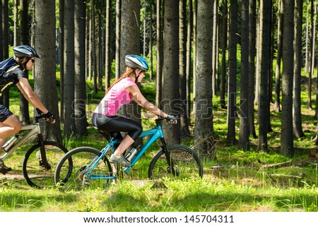 Young sporty biker couple in woods sunny day in countryside - stock photo
