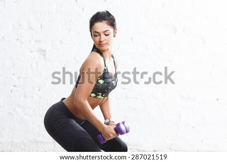 Young sporty brunette girl in sports outfits with beautiful body, doing squats with purple dumbbells, looking down, against concrete wall - stock photo