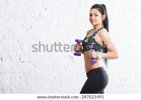 Young sporty brunette girl in sports outfits with beautiful body, holding purple dumbbells, looking at camera, against concrete wall, copy space - stock photo