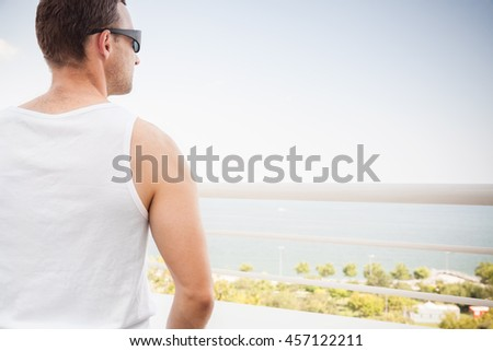 Young sporty Caucasian man in white shirt and sunglasses starring at the sea in bright summer day, rear view