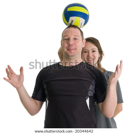 Young sporty couple. Girl is holding volleyball ball on head of her partner. Isolated over white