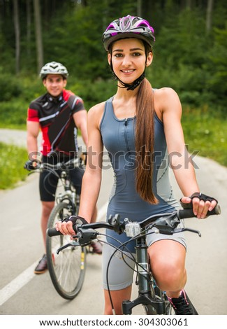 Young sporty couple riding on bicycles at the forest road. Woman in front of man.