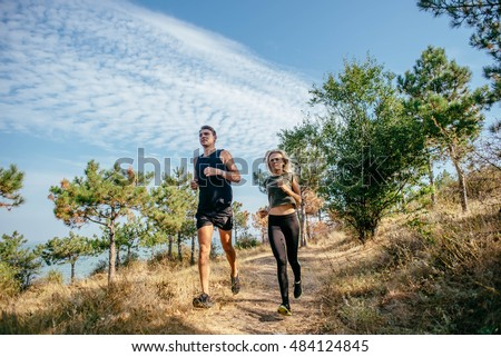 young sporty couple running in the wood