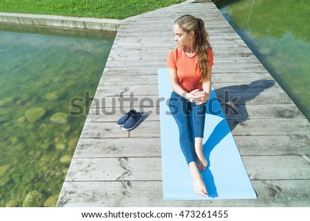 Young sporty girl preparing for the yoga next to the water