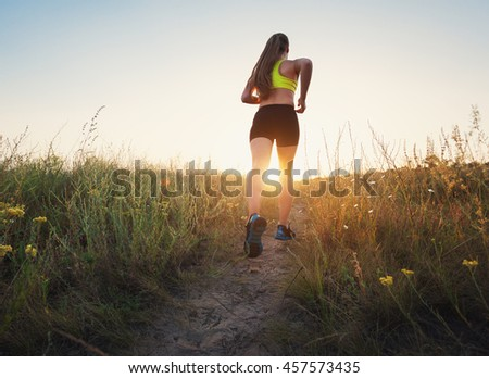 Young sporty girl running on a rural road at sunset in summer field. Athlete running on the off road in the evening. Healthy active woman. Sport and healthy lifestyle. Jogging, fitness.  - stock photo