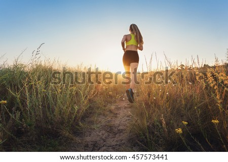Young sporty girl running on a rural road at sunset in summer field. Athlete running on the off road in the evening. Healthy active woman. Sport and healthy lifestyle. Jogging, fitness.