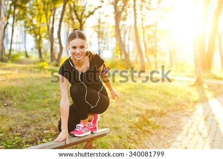 Young sporty girl with armband and earphones practicing precision and balance while sitting on a railing in park at sunset with copy space. Smiling attractive young woman athlete runner at training - stock photo