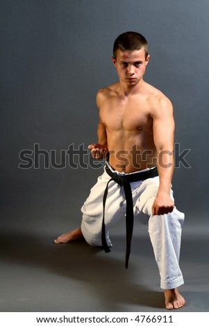 Young sporty karate man doing special exercise - stock photo