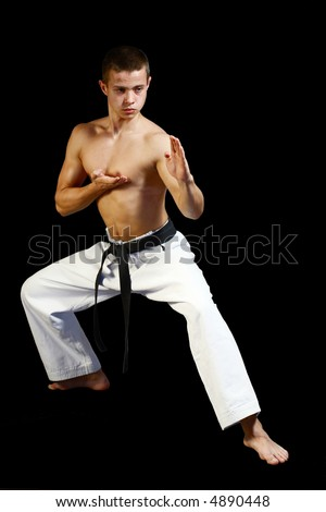 Young sporty karate man doing special exercise on black background - stock photo