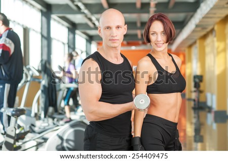 Young sporty man and woman lifting weights - stock photo