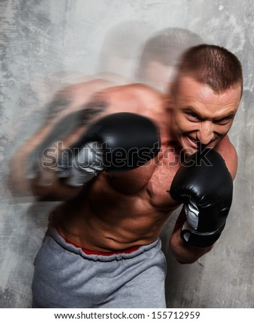 Young sporty man in boxing gloves in motion - stock photo