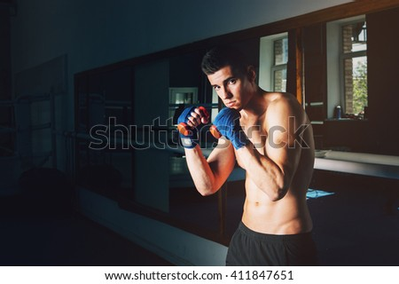 Young sporty man in the gym. Male boxer. Training. - stock photo