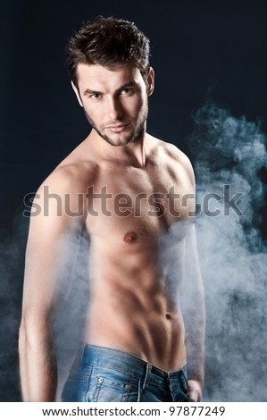 young sporty man over Smoke. Muscles, a close up - stock photo