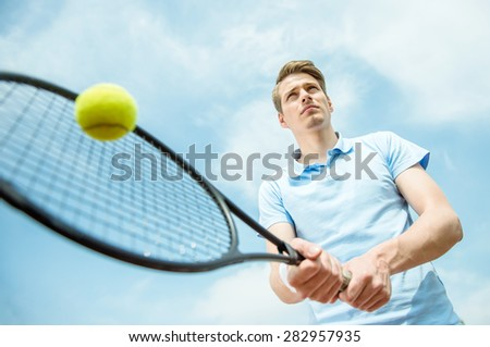 Young sporty man play tennis at court outdoors. Healthy lifestyle concept. - stock photo