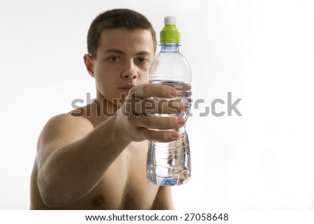 Young Sporty Man with Bottle of Pure Water on Gray Background. Focus on bottle. - stock photo