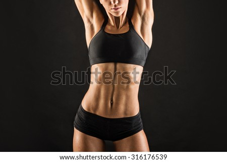 Young sporty woman close up doing stretching against black background. Grunge effect.
