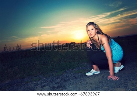 Young sporty woman crouching on a road in sunset