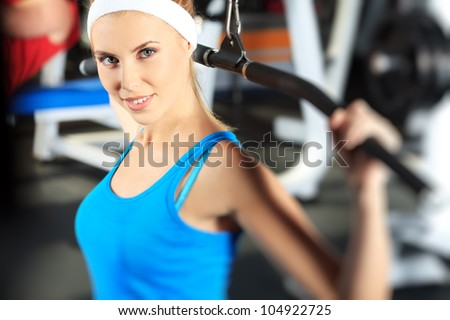 Young sporty woman doing exercises in the gym centre.