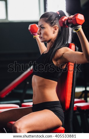 young sporty woman doing exercises with dumbbells in the gym - stock photo