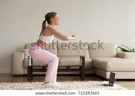 Young Sporty Woman Doing Two Leg Deep Squat Morning Exercise Standing In Living Room